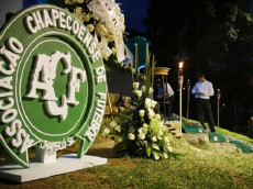 People take part in a tribute to the victims of a plane crash in the Colombian mountains in Cali, Colombia, on November 30, 2016. Emotional tributes were paid Wednesday to the Brazilian football team Chapecoense Real. The charter plane, a British Aerospace 146, reported electrical problems just before the crash as it arrived in Medellin where Chapecoense were to play in the Copa Sudamericana final. (Photo LUIS ROBAYO/AFP/Getty Images)
