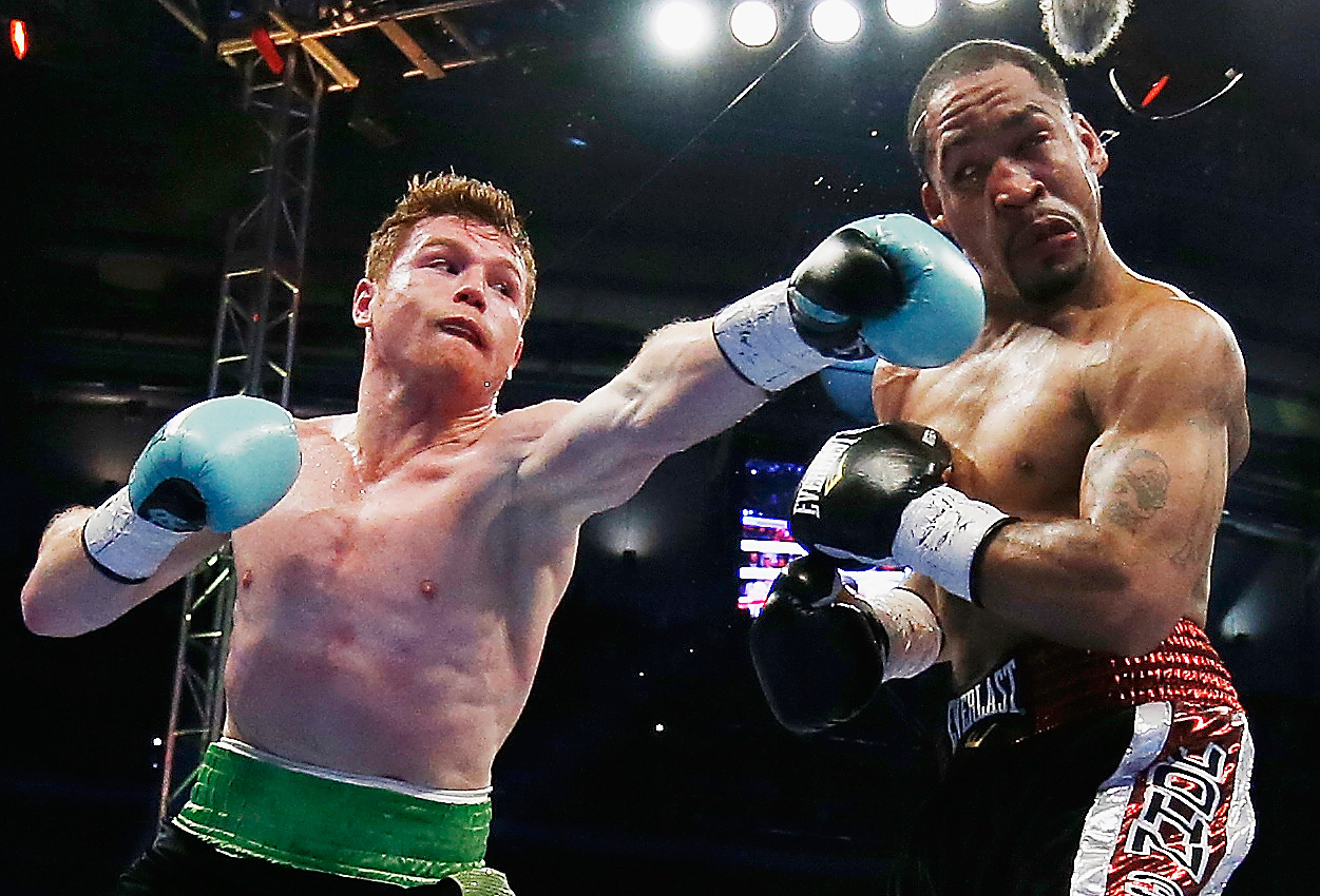 HOUSTON, TX - MAY 09:  Canelo Alvarez of Mexico (L) delivers a punch to James Kirkland during their super welterweight bout at Minute Maid Park on May 9, 2015 in Houston, Texas.  (Photo by Scott Halleran/Getty Images)