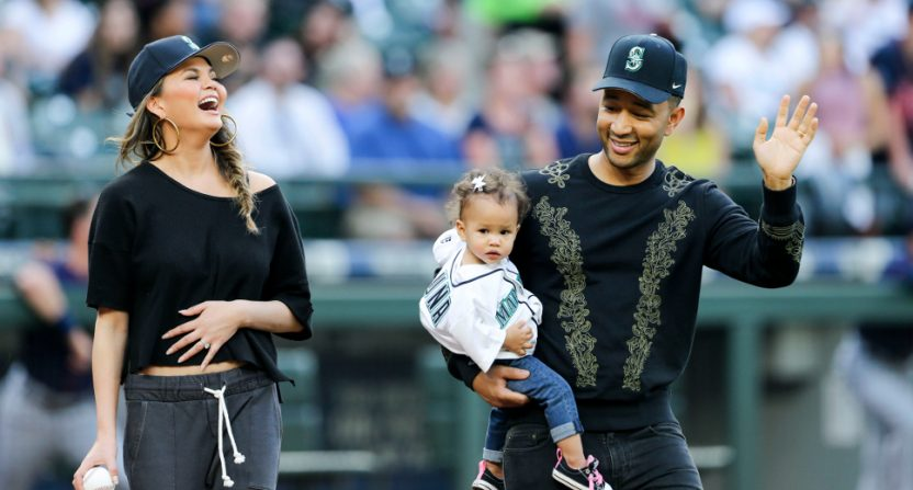 Chrissy Teigen throwing out a first pitch with husband John Legend and daughter Luna.