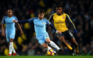 MANCHESTER, ENGLAND - DECEMBER 18:  David Silva of Manchester City (L) is put under pressure from Alex Iwobi of Arsenal (R) during the Premier League match between Manchester City and Arsenal at the Etihad Stadium on December 18, 2016 in Manchester, England.  (Photo by Clive Brunskill/Getty Images)