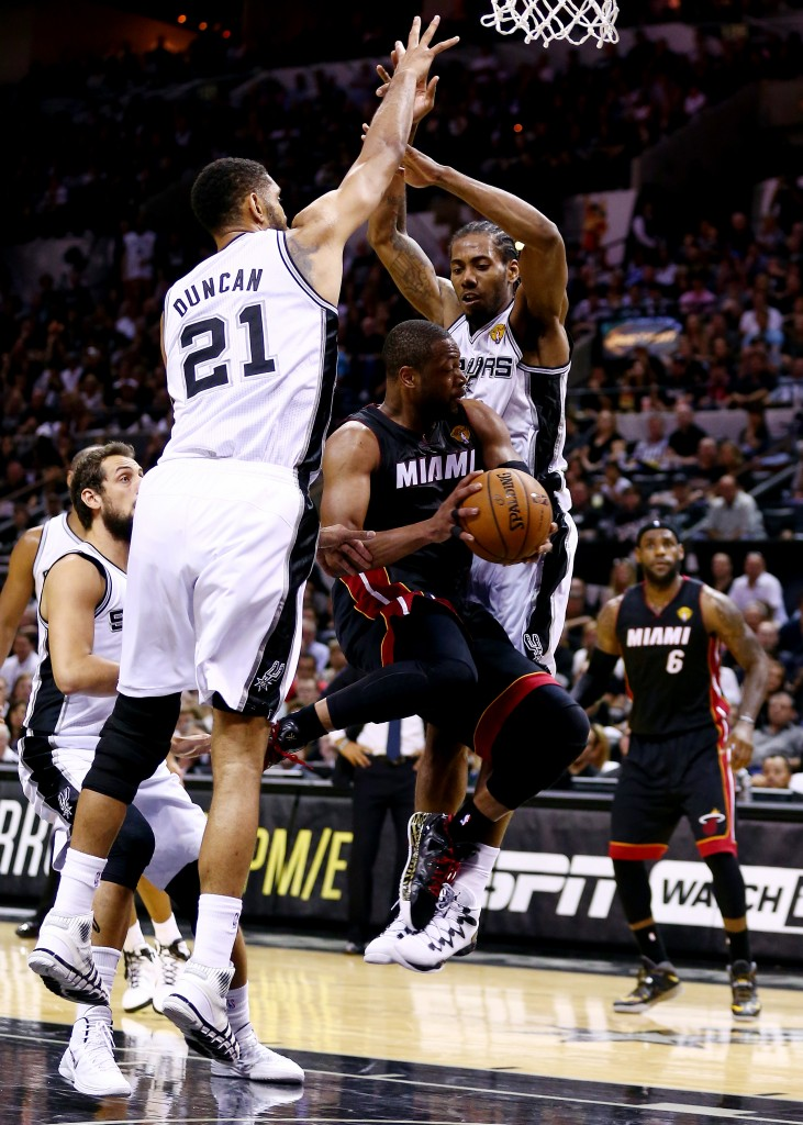 SAN ANTONIO, TX - JUNE 15: Dwyane Wade #3 of the Miami Heat goes to the basket against Tim Duncan #21 and Kawhi Leonard #2 of the San Antonio Spurs during Game Five of the 2014 NBA Finals at the AT&T Center on June 15, 2014 in San Antonio, Texas. NOTE TO USER: User expressly acknowledges and agrees that, by downloading and or using this photograph, User is consenting to the terms and conditions of the Getty Images License Agreement.  (Photo by Andy Lyons/Getty Images)