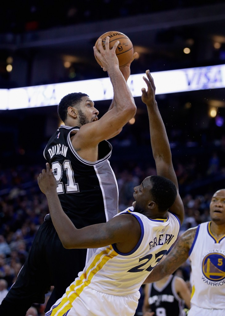 OAKLAND, CA - NOVEMBER 11:  Tim Duncan #21 of the San Antonio Spurs shoots over Draymond Green #23 of the Golden State Warriors at ORACLE Arena on November 11, 2014 in Oakland, California. NOTE TO USER: User expressly acknowledges and agrees that, by downloading and or using this photograph, User is consenting to the terms and conditions of the Getty Images License Agreement.  (Photo by Ezra Shaw/Getty Images)