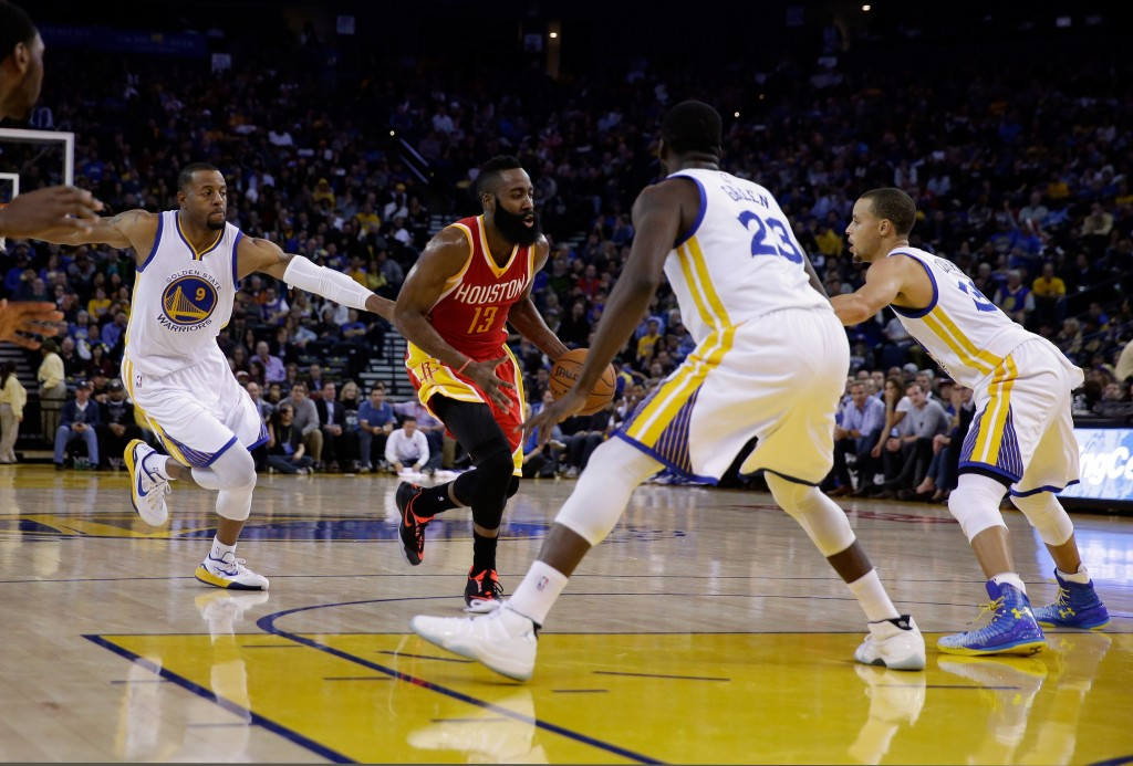 OAKLAND, CA - DECEMBER 10:  James Harden #13 of the Houston Rockets drives on Andre Iguodala #9, Draymond Green #23, and Stephen Curry #30 of the Golden State Warriors at ORACLE Arena on December 10, 2014 in Oakland, California.  NOTE TO USER: User expressly acknowledges and agrees that, by downloading and or using this photograph, User is consenting to the terms and conditions of the Getty Images License Agreement.  (Photo by Ezra Shaw/Getty Images)