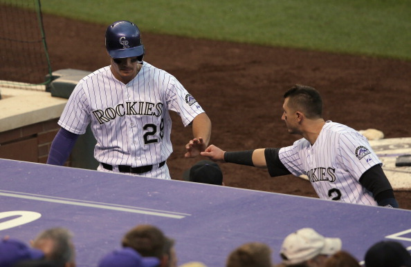 DENVER, CO - MAY 22:  Troy Tulowitzki #2 of the Colorado Rockies welcomes Nolan Arenado #28 of the Colorado Rockies back to the dugout after scoring against the San Francisco Giants to tie the score 2-2 in the fifth inning at Coors Field on May 22, 2014 in Denver, Colorado.  (Photo by Doug Pensinger/Getty Images)