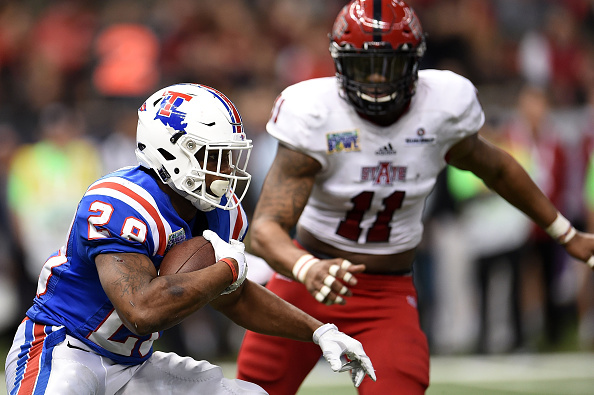 NEW ORLEANS, LA - DECEMBER 19:  Kenneth Dixon #28 of the Louisiana Tech Bulldogs is pursued by Ja'Von Rolland-Jones #11 of the Arkansas State Red Wolves during the third quarter of the R+L Carriers New Orleans Bowl at the Mercedes-Benz Superdome on December 19, 2015 in New Orleans, Louisiana.  (Photo by Stacy Revere/Getty Images)