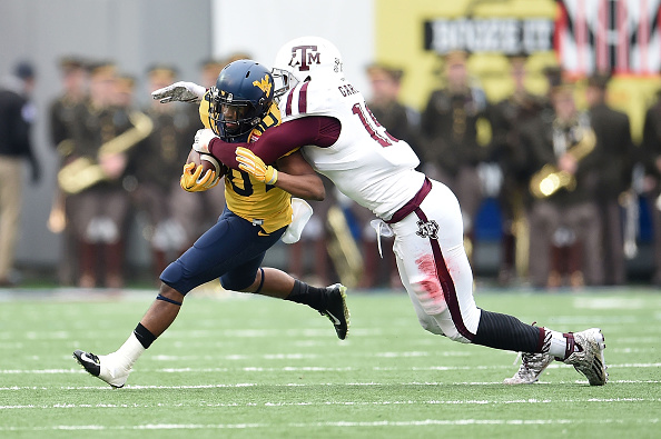 MEMPHIS, TN - DECEMBER 29:  Jordan Thompson #10 of the West Virginia Mountaineers is brought down by Myles Garrett #15 of the Texas A&M Aggies during the 56th annual Autozone Liberty Bowl at Liberty Bowl Memorial Stadium on December 29, 2014 in Memphis, Tennessee.  Texas A&M won the game 45-37.  (Photo by Stacy Revere/Getty Images)