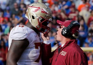 GAINESVILLE, FL - NOVEMBER 30:  Head coach Jimbo Fisher of the Florida State Seminoles grabs the facemask of Cameron Erving #75 during the game against the Florida Gators on November 30, 2013 in Gainesville, Florida.  (Photo by Sam Greenwood/Getty Images)