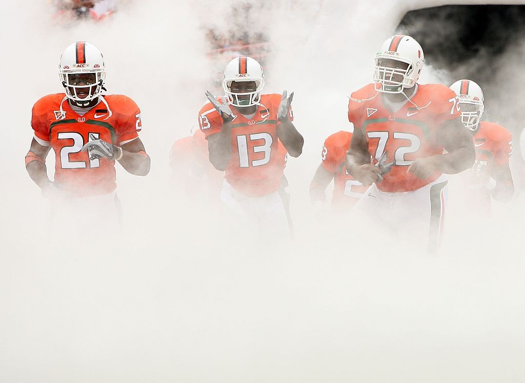 CORAL GABLES, FL - OCTOBER 13:  Derron Thomas #21, Ryan Hill #13 and Andrew Bain of the Miami Hurricanes run out of the tunnel prior to taking on the Georgia Tech Yellow Jackets at the Orange Bowl on October 13, 2007 in Coral Gables, Florida.  (Photo by Doug Benc/Getty Images)