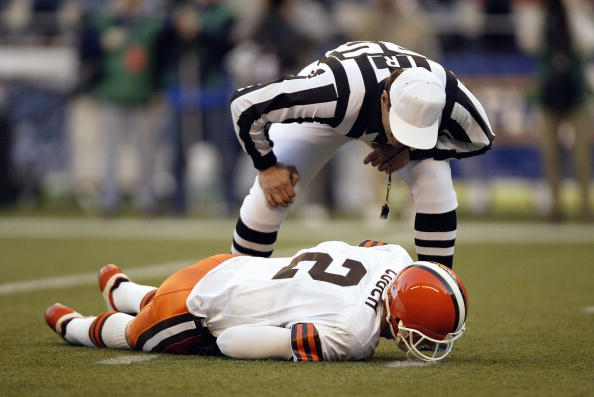 SEATTLE - NOVEMBER 30:  Referee Ed Hochuli #85 looks to help Quarterback Tim Couch #2 of the Cleveland Browns as he lays hurt during the game against the Seattle Seahawks on November 30 2003 at Seahawks Stadium in Seattle, Washington. The Seahawks defeated the Browns 34-7. (Photo by Otto Greule Jr/Getty Images)