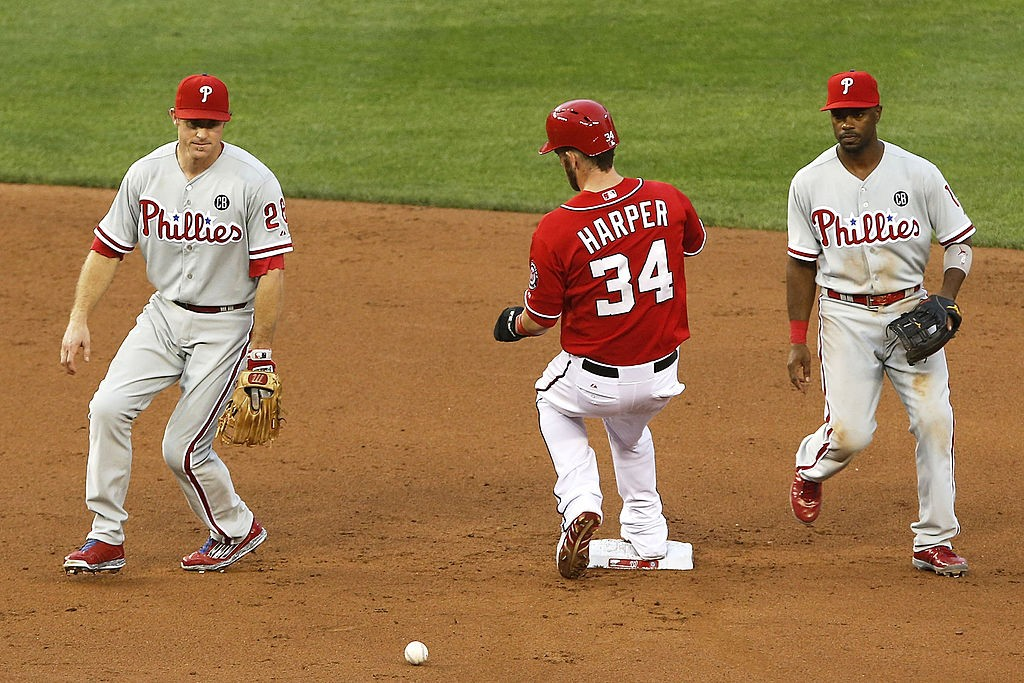 WASHINGTON, DC - AUGUST 02:  Bryce Harper #34 (C) of the Washington Nationals is safe at second after Chase Utley #26 (L) committed an error on a ground ball hit by Asdrubal Cabrera in the second inning at Nationals Park on August 2, 2014 in Washington, DC. Also pictured is shortstop Jimmy Rollins #11 of the Phillies (R). (Photo by Jonathan Ernst/Getty Images)
