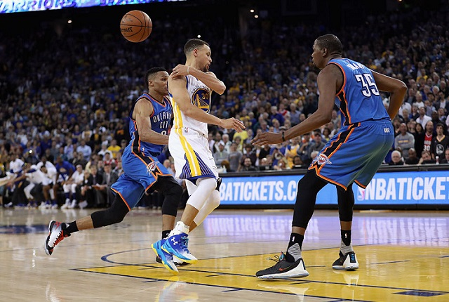 OAKLAND, CA - MARCH 03: Stephen Curry #30 of the Golden State Warriors passes the ball while guarded by Russell Westbrook #0 and Kevin Durant #35 of the Oklahoma City Thunder at ORACLE Arena on March 3, 2016 in Oakland, California. (Photo by Ezra Shaw/Getty Images)