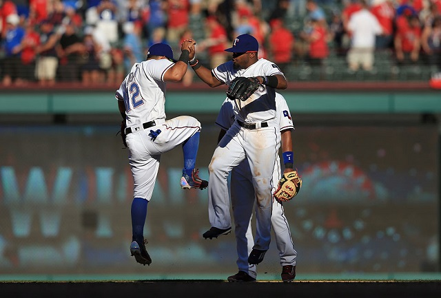ARLINGTON, TEXAS - APRIL 04: Rougned Odor #12 of the Texas Rangers, Elvis Andrus #1 of the Texas Rangers and Delino DeShields #3 of the Texas Rangers celebrate after beating the Seattle Mariners 3-2 on Opening Day at Globe Life Park in Arlington on April 4, 2016 in Arlington, Texas. (Photo by Tom Pennington/Getty Images)