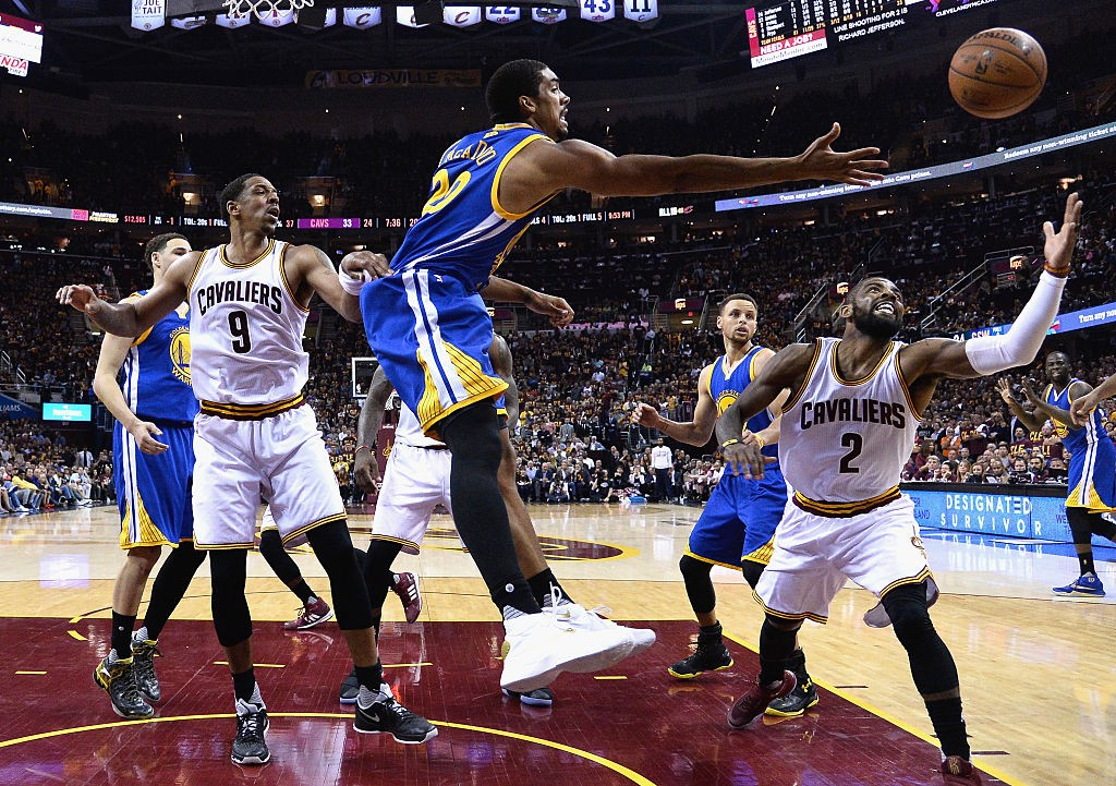 CLEVELAND, OH - JUNE 10: James Michael McAdoo #20 of the Golden State Warriors and Kyrie Irving #2 of the Cleveland Cavaliers reach for the ball during the first half in Game 4 of the 2016 NBA Finals at Quicken Loans Arena on June 10, 2016 in Cleveland, Ohio. (Photo by Larry W. Smith - Pool/Getty Images)