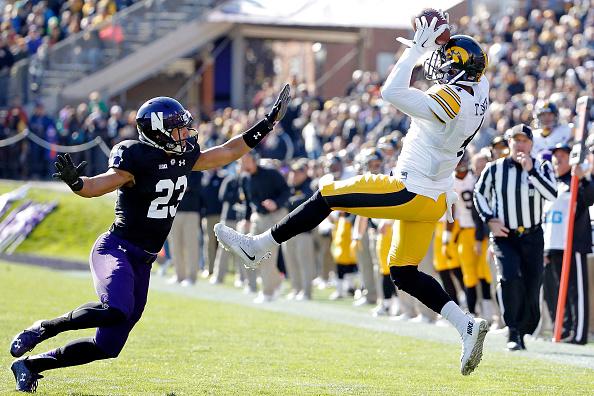 EVANSTON, IL - OCTOBER 17: Tevaun Smith #4 of the Iowa Hawkeyes makes a catch while defended by Nick VanHoose #23 of the Northwestern Wildcats during the first quarter at Ryan Field on October 17, 2015 in Evanston, Illinois.  (Photo by Jon Durr/Getty Images)