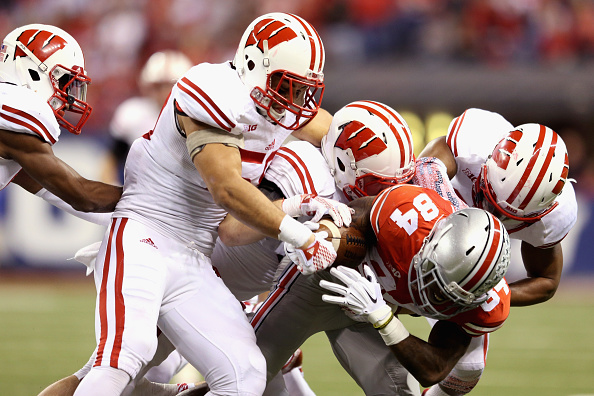 INDIANAPOLIS, IN - DECEMBER 06:  Corey Smith #84 of the Ohio State Buckeyes is tackled by the Wisconsin Badgers during the Big Ten Championship at Lucas Oil Stadium on December 6, 2014 in Indianapolis, Indiana.  (Photo by Andy Lyons/Getty Images)