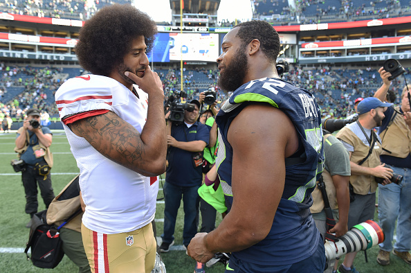 SEATTLE, WA - SEPTEMBER 25: Quarterback Colin Kaepernick #7 of the San Francisco 49ers speaks with defensive end Michael Bennett #72 of the Seattle Seahawks after the game at CenturyLink Field on September 25, 2016 in Seattle,Washington. The Seahawks won the game 37-18.  (Photo by Steve Dykes/Getty Images)