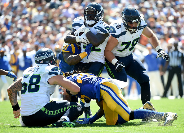 LOS ANGELES, CA - SEPTEMBER 18:  Christine Michael #32 of the Seattle Seahawks runs as he is tackled by Dominique Easley #91 of the Los Angeles Rams during the second quarter of the home opening NFL game between the Los Angeles Rams and the Seattle Seahawks at Los Angeles Coliseum on September 18, 2016 in Los Angeles, California.  (Photo by Harry How/Getty Images)