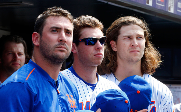 NEW YORK, NY - JULY 12:  (L-R) Matt Harvey #33, Steven Matz #32 and Jacob deGrom #48 of the New York Mets look on against the Arizona Diamondbacks at Citi Field on July 12, 2015 in the Flushing neighborhood of the Queens borough of New York City. The Mets defeated the Diamondbacks 5-3.  (Photo by Jim McIsaac/Getty Images)