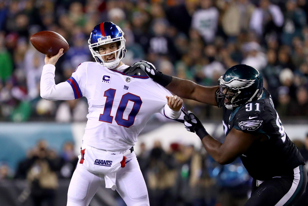 PHILADELPHIA, PA - DECEMBER 22:  Quarterback Eli Manning #10 of the New York Giants looks to throw a pass against defensive tackle Fletcher Cox #91 of the Philadelphia Eagles during the second quarter of the game at Lincoln Financial Field on December 22, 2016 in Philadelphia, Pennsylvania.  (Photo by Al Bello/Getty Images)