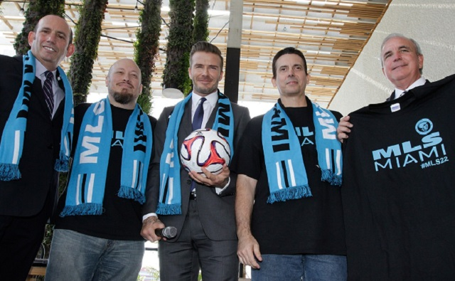 Former  England and Manchester United star, David Beckham(C) poses for photos after holding a press conference at the Perez Art Museum Miami, in Miami, Florida on February 5, 2014. Beckham said Wednesday that he will buy a US team to play Major League Soccer and bring it to Miami, confirming the worst-kept secret in world football. At left is Major League Soccer Commissioner, Don Garber(L) and Miami-Dade County Mayor, Carlos A. Gimenez is at right. AFP PHOTO / Alexia FODEREAlexia Fodere/AFP/Getty Images