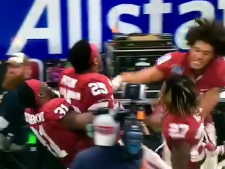 Joe Mixon gets punched by Oklahoma teammates in celebration.