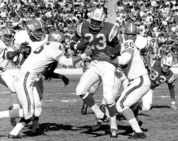 San Diego Chargers halfback Paul Lowe (23) is met by many defenders during a 58-20 victory over the Denver Broncos on December 22, 1963, at Balboa Stadium in San Diego, California. (Photo by Charles Aqua Viva/Getty Images)
