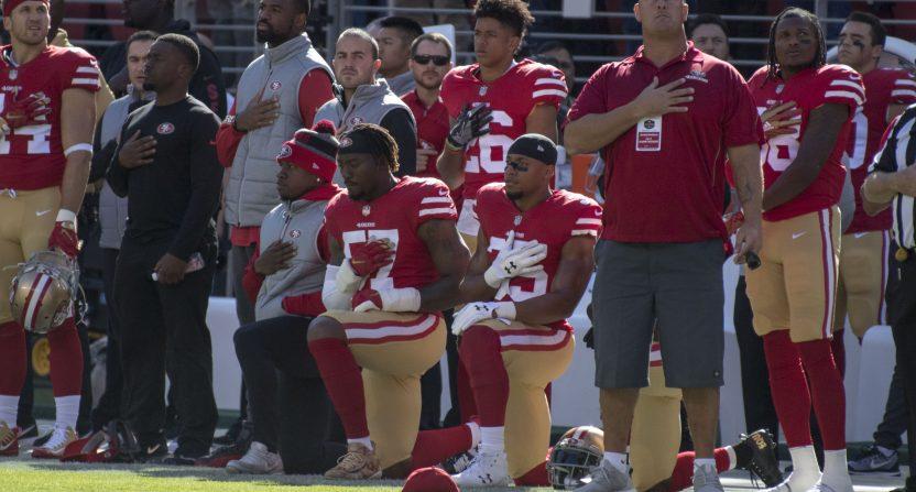Eli Harold and Eric Reid kneel during the anthem in November 2017.