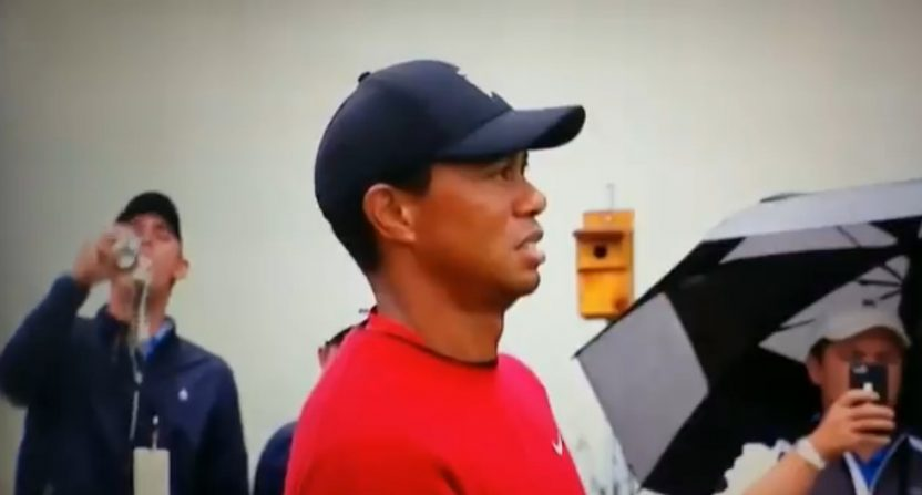 A fan chugging a beer behind Tiger Woods at the 2018 BMW Championship.