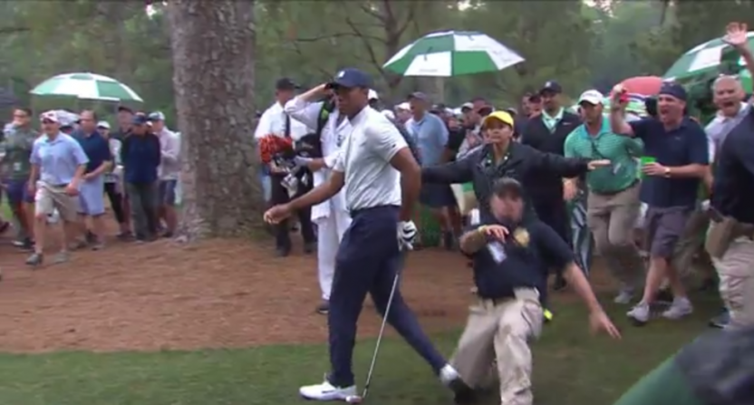 A security guard sliding into Tiger Woods at the Masters.