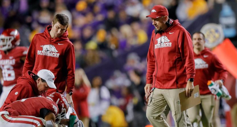 Arkansas interim head coach Barry Lunney Jr. checks on an injured player in a game against LSU.