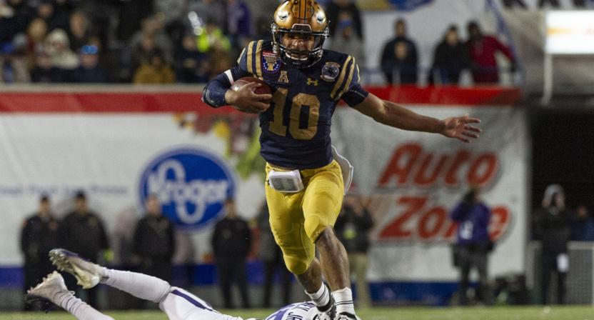 Navy QB Malcolm Perry hurdles a Kansas State defender at the Liberty Bowl.