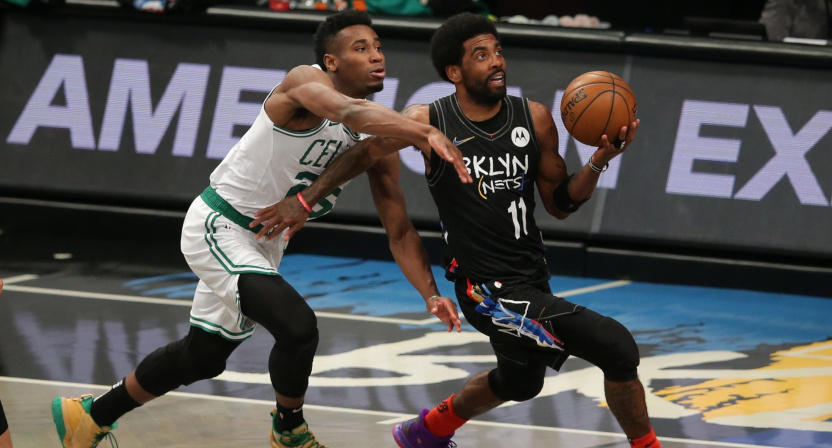 Nets' point guard Kyrie Irving drives against Aaron Nesmith.