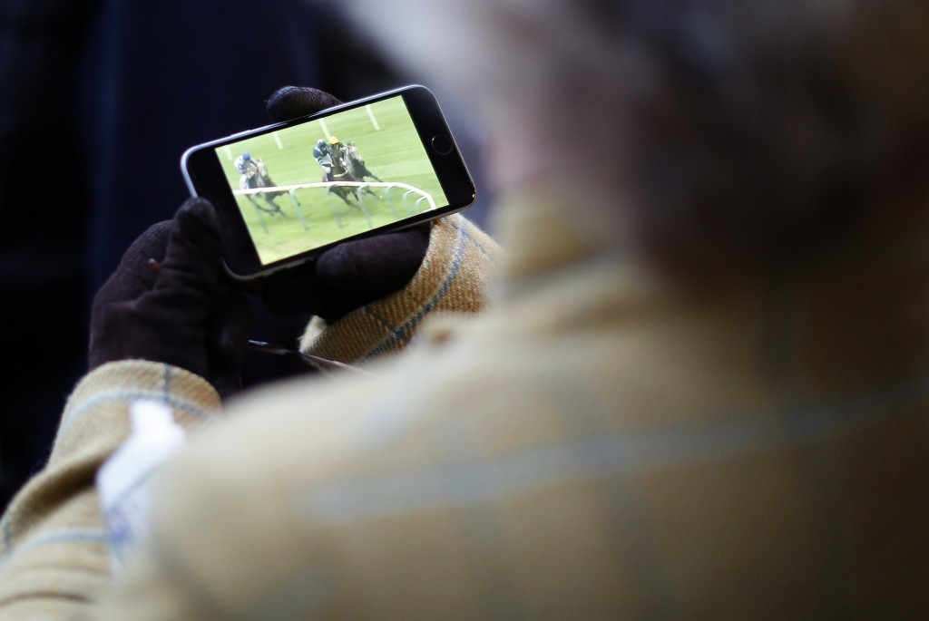 CHELTENHAM, ENGLAND - OCTOBER 23:A racegoer watches some action on her phone at Cheltenham racecourse on October 23, 2015 in Cheltenham, England. (Photo by Alan Crowhurst/Getty Images)
