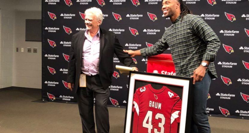 Larry Fitzgerald presenting Bob Baum with a jersey.