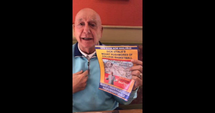 Dick Vitale with a poster for his new book. He's donating his proceeds to The V Foundation.