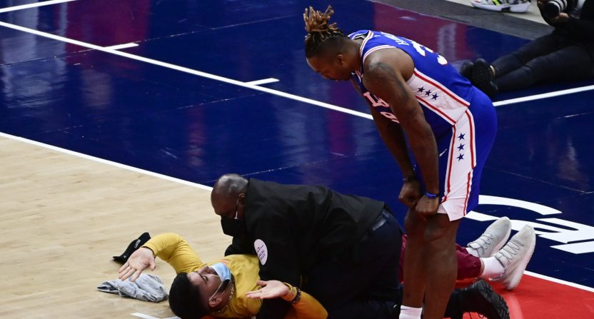 A security guard pins a fan who invaded the court as Dwight Howard looks on.